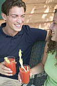 Young couple with tomato drinks out of doors