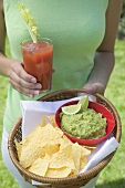 Woman holding tomato drink & basket of guacamole & chips