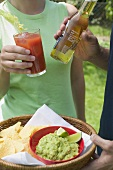 Young couple with guacamole, chips and drinks