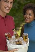 Mann hält Eiskübel mit Bierflaschen, Frau im Hintergrund