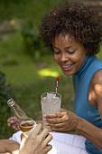 Frau mit Glas Limonade beim Gartenfest