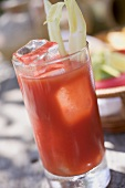 Tomato drink with celery and ice cubes