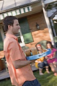 Man serving tray of iced tea and snacks in garden