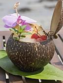 Kokosnussdrink mit Ananas, Cocktailkirsche und Orchidee