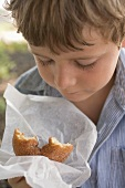Small boy holding doughnut in paper