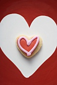 An iced, heart-shaped biscuit in a white heart