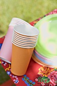 Coloured paper cups and plates on folding stool in garden