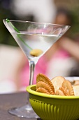 Martini with green olive, crackers, woman in background