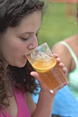 Woman drinking a glass of iced tea