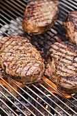 Several beef steaks on a barbecue grill rack