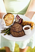 Woman holding a plate of grilled steak and accompaniments