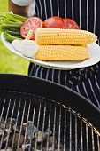 Person holding plate of vegetables & corn on the cob for grilling