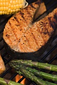 Salmon steak and vegetables on a barbecue