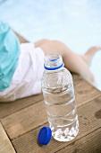 Kind sitzt neben Wasserflasche am Schwimmbecken