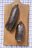 Two black puddings on chopping board (overhead view)