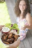 Hände servieren gegrillte Chicken Wings, Frau im Hintergrund