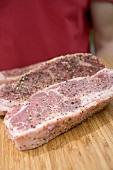 Seasoned steaks on chopping board, man in background