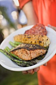Woman holding plate of grilled salmon, corn on the cob & vegetables