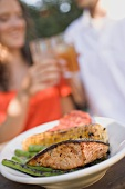 Grilled salmon with accompaniments, couple clinking glasses
