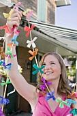 Frau mit bunten Girlanden fürs Gartenfest