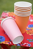 Coloured paper cups on folding stool in garden