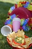 Guacamole with tortilla chips, paper cups, coloured garlands