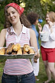 Young woman serving grilled corn on the cob at a barbecue