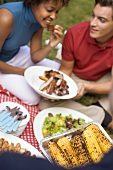 Couple with grilled spare ribs, corn on the cob, salad, on grass