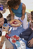 Young people with blueberry pie & doughnuts on the 4th of July