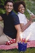Paar mit Wunderkerzen beim Picknick am 4th of July (USA)