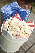 Hand holding wooden bucket full of popcorn (4th of July, USA)