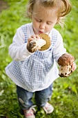 Small girl holding two fresh ceps