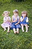 Three children with ice cream cones sitting on grass