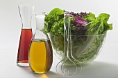 Oil & vinegar in carafes beside salad bowl, salad servers