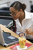 Woman eating fruit salad in the office