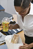 Woman with packed lunch (sandwich, fruit salad) in the office