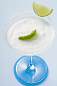 Margarita with lime wedges in a glass with a salted rim