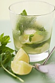 Glass of Mojito with lime & mint, surrounded by ingredients