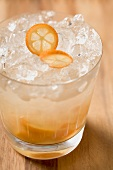 Cocktail with kumquats and ice cubes