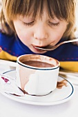 Child slurping cocoa from a spoon