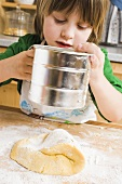 Child sifting flour onto dough