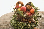 Gingerbread, fruit, nuts and cones in basket on box wreath