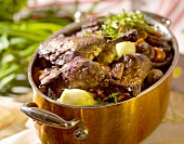 Braised duck legs with vegetables in a copper pot