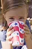 Small girl drinking out of a paper cup (4th of July, USA)