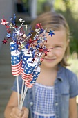 Small girl holding 4th of July decorations (USA)