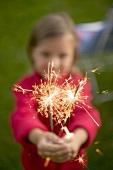 Small girl holding sparklers in garden