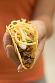 Hand holding a taco filled with mince and cheese