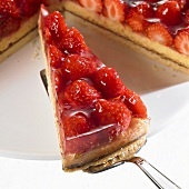 Piece of strawberry flan on server in front of remainder of flan