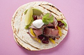 Beef fajita with beans, peppers and sour cream