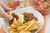 Hand dipping tortilla chip in mince sauce, salsa at side